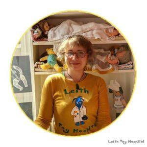 Karlyn is at Leith Toy Hospital in front of some dolls in little beds. She is wearing a yellow T shirt with the Toy Hospital logo on.